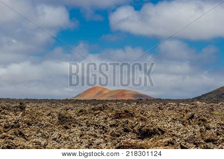 Landscape of Timanfaya National Park in Lanzarote, Canary Islands, Spain. Red and black volcanic mountains.