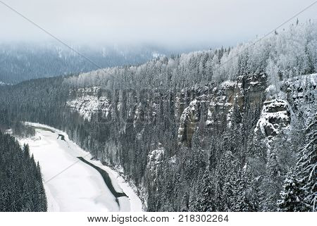 The view from the top of the rock to the frozen river flowing among the cliffs in the winter snow-covered gloomy landscape