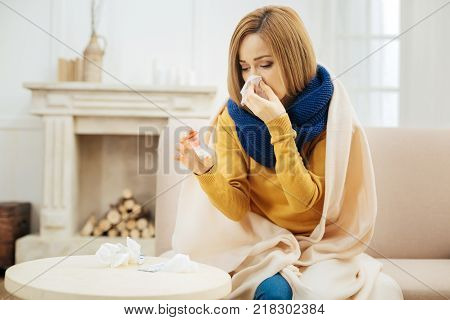Taking drugs. Cheerless unwell young blond woman having fever and blowing her nose and holding medication while having a blanket on her shoulders and sitting on the couch