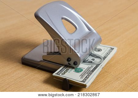 paper banknote in a hole punch for paper. the business concept of wasting a large company a non-standard image. fantasy picture with dollars.