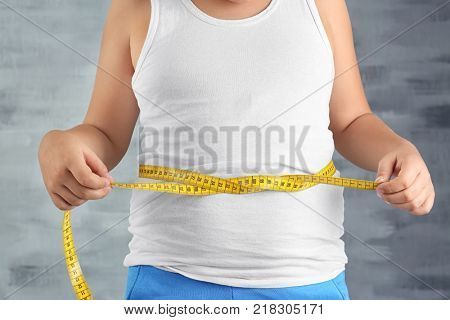 Overweight boy measuring waist on grey background, closeup