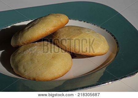 Old fashioned sugar cookies in the golden natural light of a winter's day with the setting sun casting shadows on a plate. The cookies are made of sugar, flour, butter, eggs, vanilla, baking soda.