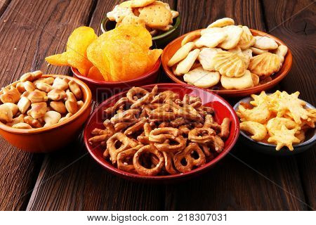 Salty snacks. Pretzels chips crackers on brown wooden backgroun d