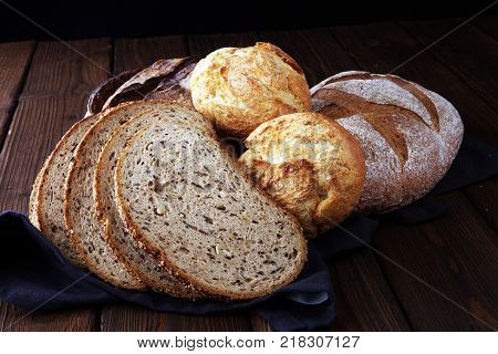 Different kinds of bread and bread rolls on brown wooden table. Kitchen or bakery poster design.