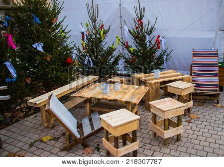 Tables and chairs from the remains of a tree and Christmas trees decorated with bows of ribbons installed on the street. Concept ecology and economy.