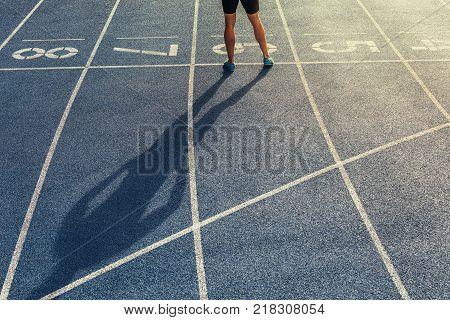 Sprinter Standing On Starting Block On Running Track
