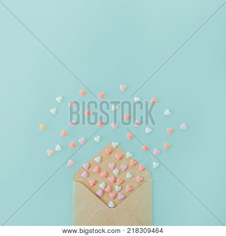 Multicolor sweets sugar candy hearts fly out of craft paper envelope on the light blue background . Valentine day. love concept. Gift message for lover. Space for text. Square banner
