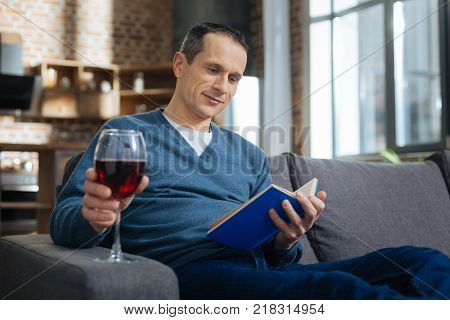 Warm atmosphere. Positive delighted brunette keeping smile on his face and looking at book while holding bocal with wine
