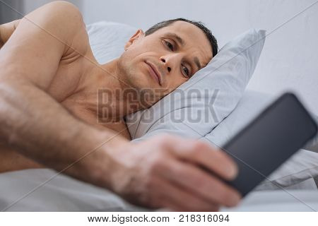 Want to sleep. Tired brunette man opening eyes and looking at telephone while going to get up