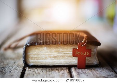 Cross with Bible,Closeup of wooden christian cross and bible on the old wooden background.