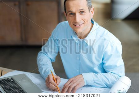 Conscious worker. Handsome male person feeling happiness while raising head and posing on camera