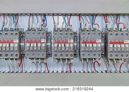 Several electrical contactor on a mounting panel in electrical closet. Modern contactors to start motors pumps and other equipment. Contactors connected to the wires marked.