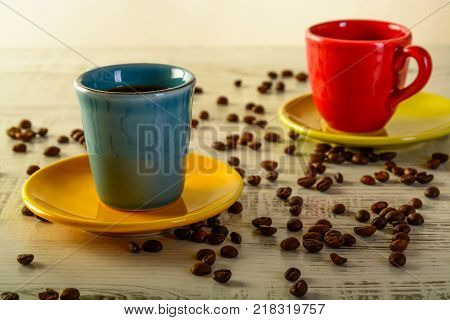 two coffee cups with diferent colors with coffee beans liyng in the background