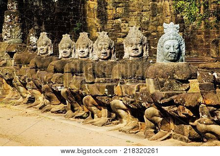 A row of asuras or demons at Angkor Thom South Gate. The South Gate of Angkor Thom is one of the five gateways into the ancient Khmer city of Angkor Thom. The South Gate is the most visited of the five Angkor Thom gates as it is the one nearest to Angkor
