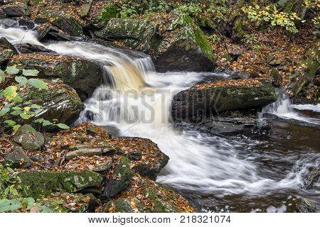 Whitewater splashes down a rocky autumn watercourse in Ganoga Glen Ricketts Glen State Park Pennsylvania.