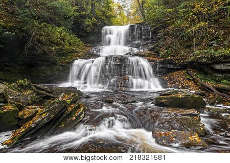 Tuscarora Falls splashed down the rocky cliffs covered with autumn leaves of Ganoga Glen in Ricketts Glen State Park Pennsylvania.