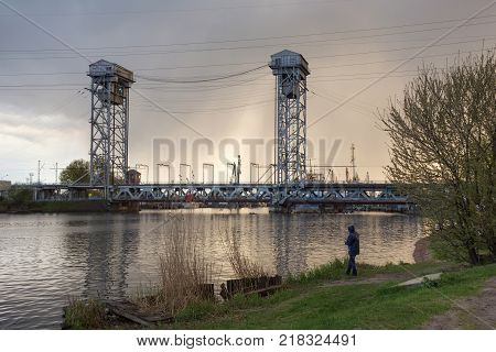 Fisherman near steel double-deck drawbridge over the Pregolya River in Kaliningrad (Konigsberg) Russia. The bridge was built in the 1913-1926 and was reconstructed in 1959-1965.