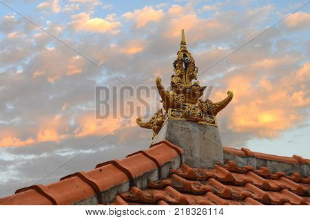 A gold-colored ornate roof pinnacle depicting elephants and tigers facing North South East and West atop a family's home. Ubud Bali - September 2015