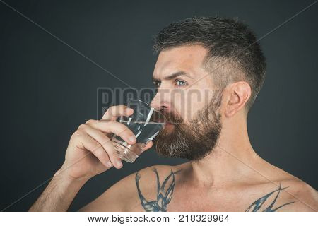 Health and dieting. Hipster drink clean healthy water refreshing. Man with long beard hold water glass on grey background. Hangover and thirst. Life source and healthcare. poster