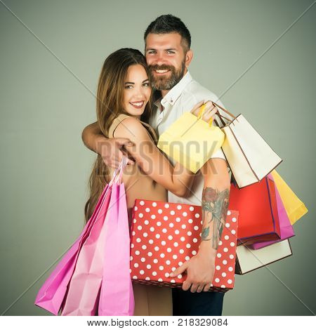 Fashion shopaholic couple. Couple in love hold shopping bag near grey wall. Black Friday happy holiday relations. Girl and bearded man hold present pack cyber Monday. Shopping and sale.
