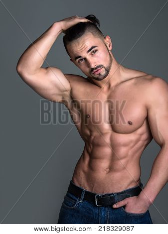 Sport and workout. Man with muscular body and torso. Athletic bodybuilder man on grey background. Coach sportsman with bare chest in jeans. Dieting and fitness.