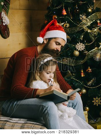 Santa claus kid and bearded man at Christmas tree. Christmas happy child and father read book. New year small girl and man fairytale. Xmas party celebration fathers day. Winter holiday and vacation.