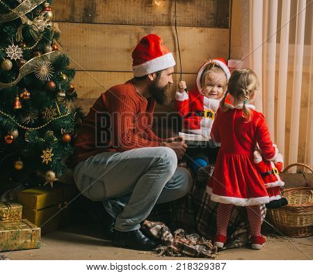 New year small girl and man fairytale. Xmas celebration fathers day. Christmas happy children and father read book. Santa claus kid and bearded man at Christmas tree. Winter holiday and vacation.