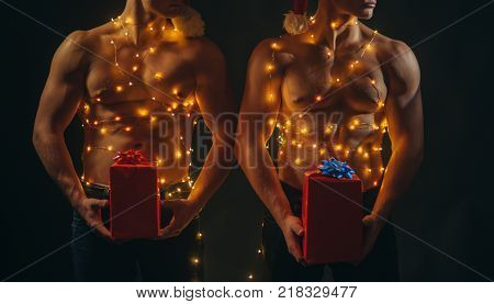 Twins santa with muscular body in garland. New year strip and gifts for adults. Young men in santa costume present for girls. Christmas party and sex games. Call boys or sexy athlete men at xmas.