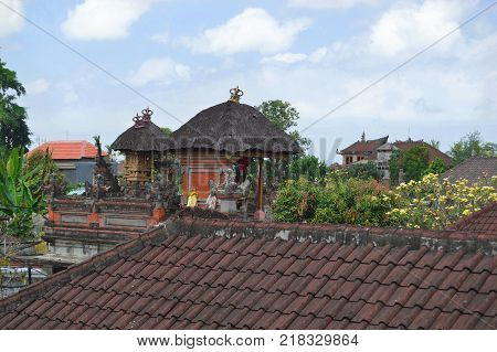 Rooftop View of Thatched Roof Shrines in Ubud The people of Bali envelope themselves in their religion. Many families have shrines built on the rooftops of their homes and businesses. August 2015