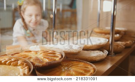 Girl with a pigtail looks at the pies in the window choosing, the girl on the other hand showcases, de-focused view