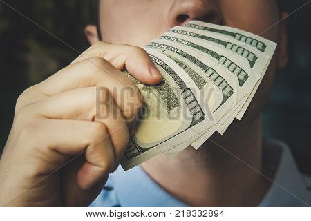 Handsome young businessman holding and smelling money. the smell of money. 500 dollars