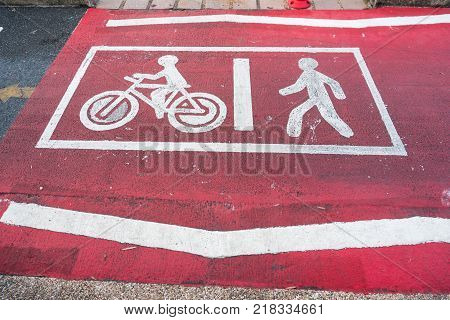 Painted signs on asphalt for pedestrian and bicycle lanes with red background