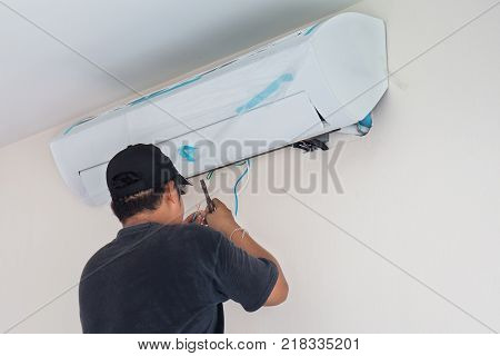 Man worker installs indoor air conditioner in the new home. Select focus