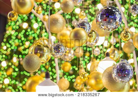 Golden Christmas Ball Hanging On Christmas Tree With Green Bokeh In Night Time