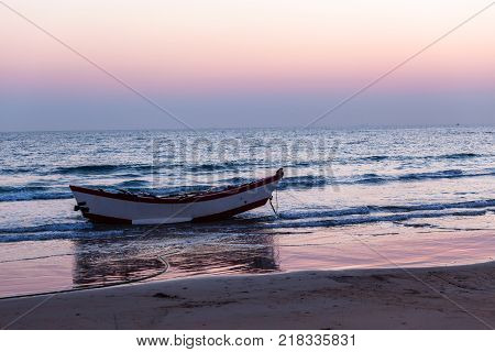 Old vintage fishing netting boat with oars beach shallows water line morning dawn ocean horizon landscape