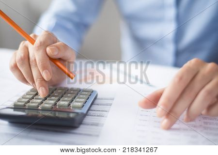 Close-up of manager calculating data during paperwork. Banking specialist examining list of customer and carrying out their debit and credit. Audit concept