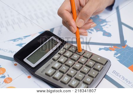Accounting manager working on annual report and using calculator at desk. Close-up of businesswoman counting gains and losses examining financial report. Audit concept