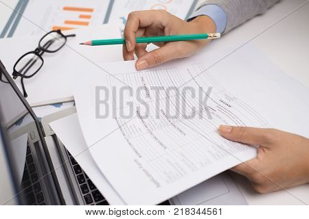 Sales manager preparing report for annual meeting and reading document at table. Close-up of businesswoman editing papers. Workspace concept