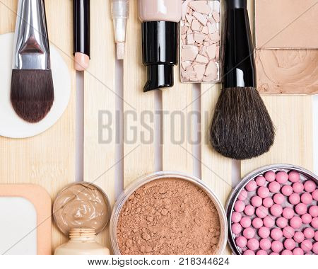 Essential make-up products to create the perfect complexion, top view. Primer, concealer, foundation, cosmetic powder, blusher with makeup brushes and sponges