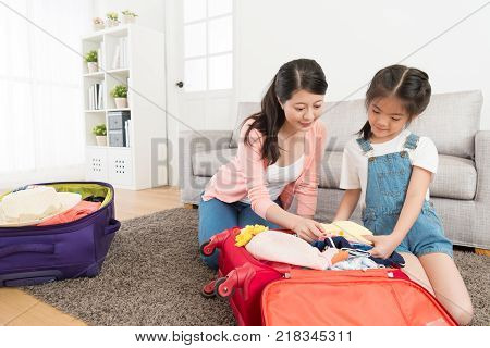 Mother With Little Daughter Packing Suitcase