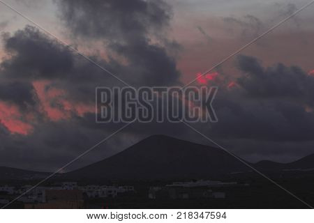 Sunset and sunrise. Orange and red colors. rock area. Volcanic area in Lanzarote national park. Mountain silhouette