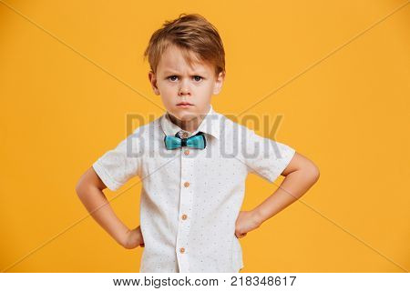 Photo of angry little boy child standing isolated over yellow background. Looking camera.
