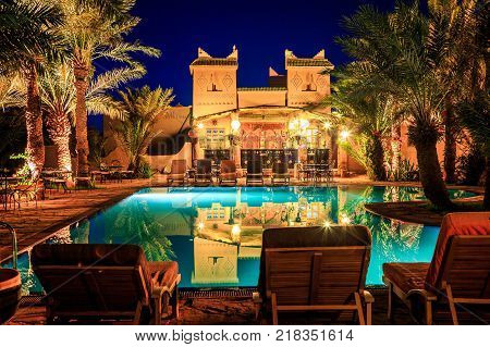 M'hamid Morocco - February 22 2016: view of pool bar in Chez le Pacha hotel with typical decoration with reflection in the poo and deck chairl in front