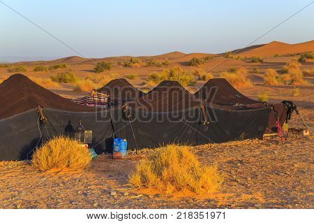 Merzouga Morocco - February 25 2016: Moroccan Sahara Desert Camp with the Sahara Desert in the background. Merzouga is famous for its dunes the highest in Morocco.
