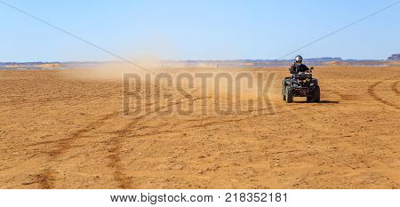 Ait Saoun Morocco - February 22 2016: panoramic view of man riding atv quad bike on sand in desert on a sunny day in Ait Saoun desert in Morocco.