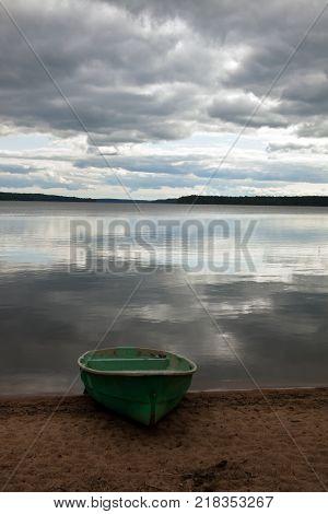 Boat on lake in autumn in cloudy weather. Pioneer lake in September. Leningrad region Russia