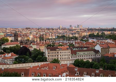 View of buildings at Mala Strana (Lesser Town), Old Town and beyond in Prague, Czech Republic, viewed slightly from above at sunset.