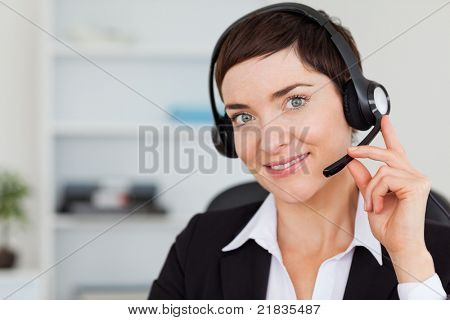 Close up of a smiling secretary calling with a headset in her office
