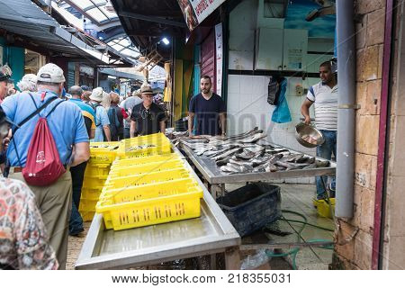 Acre Israel November 03 2017 : The seller offers the customers fresh fish on the market in the old city of Acre in Israel