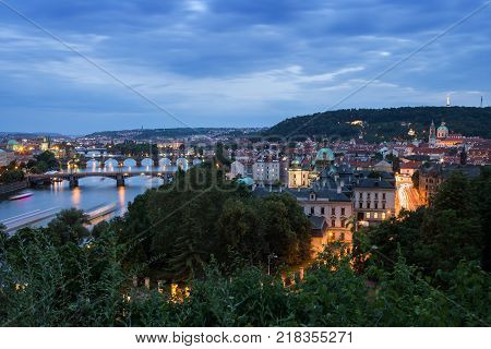 Bridges over Vltava River and buildings at the Mala Strana District (Lesser Town) in Prague, Czech Republic, viewed slightly from above in the evening.
